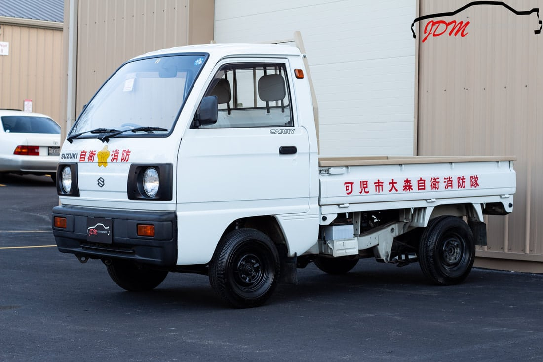 The different bed types of a Kei truck includes the flatbed, a standard for Kei Truck models. Image of a white flatbed Kei.