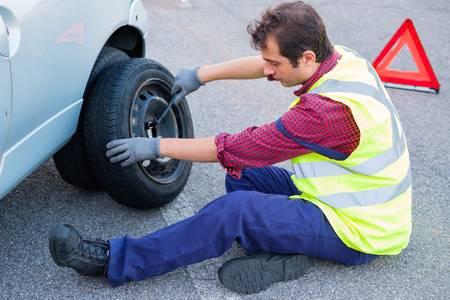 Man Changing A Flat Tyre After Vehicle Breakdown Stock Photo, Picture And  Royalty Free Image. Image 85193264.